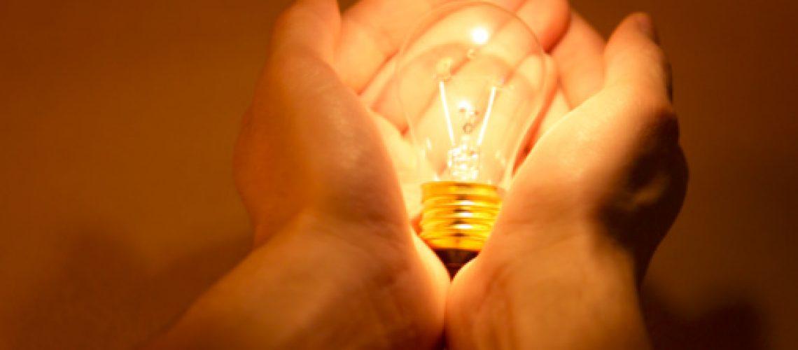 Person holding an illuminated light bulb