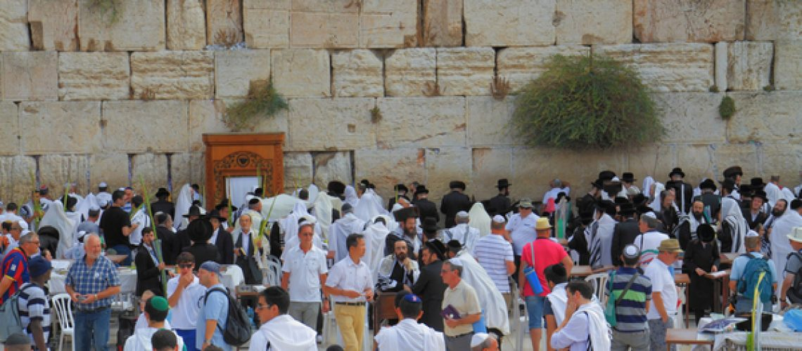JERUSALEM, ISRAEL - SEPTEMBER 18, 2013: Sunny morning in the holiday of Sukkot. Religious Jews in white prayer shawls are going to pray at the Western Wall of the Temple